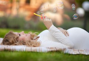 A happy pregnant woman relaxing outdoors in nature