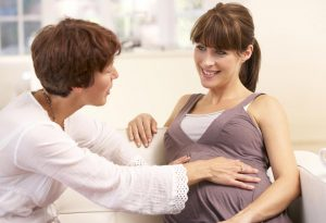 A pregnant woman getting support from a midwife