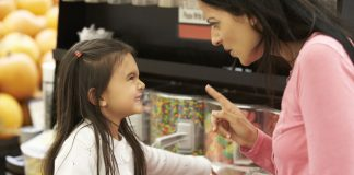 A mother shouting at her daughter at a candy store
