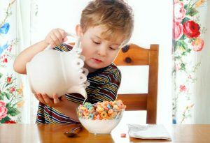A child preparing a bowl of cereal on his own
