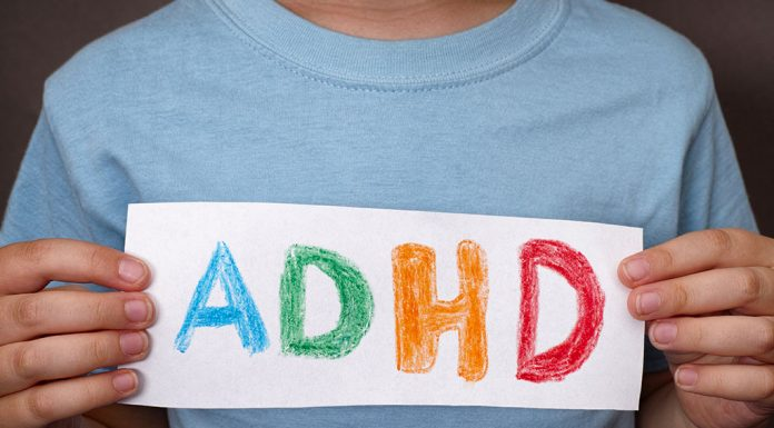 A little boy holding a piece of paper with ADHD written on it