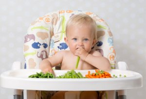 Baby eating a variety of vegetables