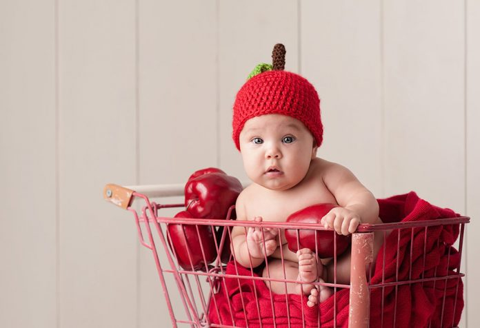 A baby wearing an apple hat