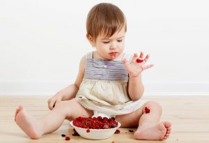 A baby eating strawberry
