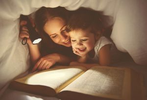 A mother and daughter reading a book under the flashlight at night