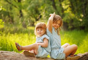 Two sisters sitting in a park on a summer day.
