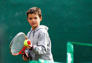 A little boy playing tennis