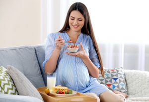 A pregnant woman eating healthy foods