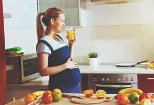 A pregnant woman drinking juice