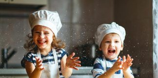 A little girl and a boy playing with cookie dough in the kitchen