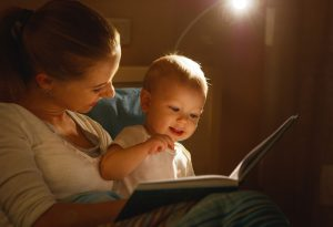 MOTHER READING OUT TO BABY