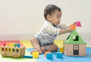 A none month-old baby playing all by himself