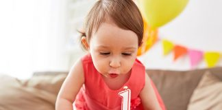 A one year-old girl blowing off her birthday candle