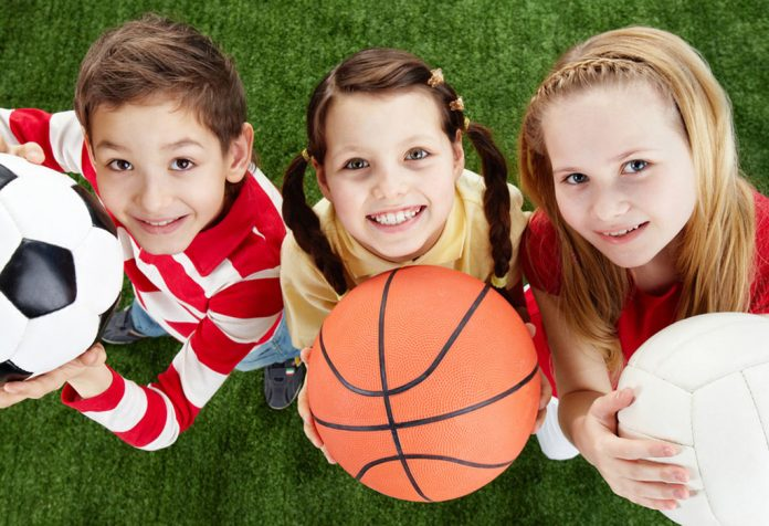 Three kids holding balls on the grass