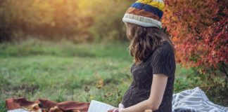 A pregnant woman reading a book while sitting in a park