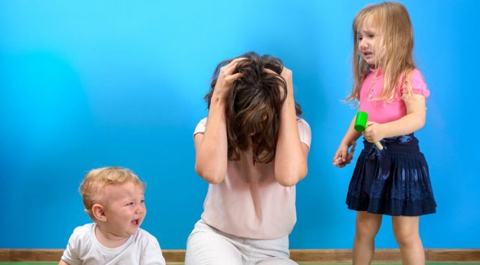 A frustrated mother dealing with two aggressive children
