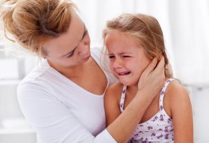 Girl crying as mother consoles