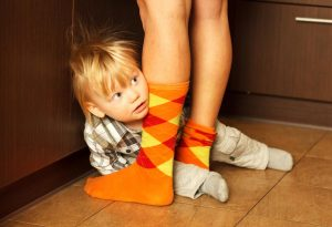 Socially awkward child hiding behind mother's legs