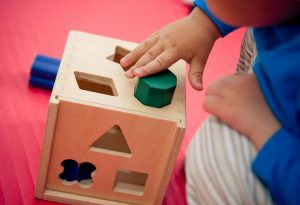 A baby playing with shapes-learning toys