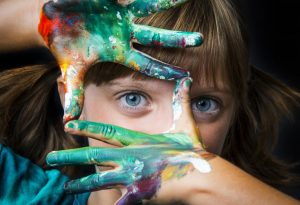 A little girl with her hands smeared in water colours
