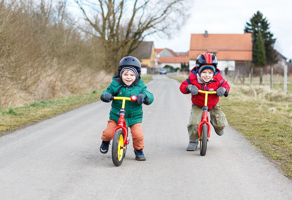 Toddlers cycling outdoors