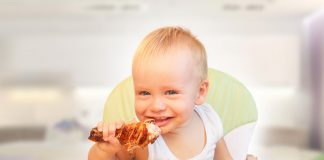 A baby eating chicken