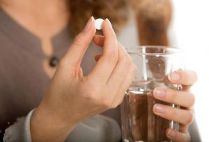 A woman holding a pill and a glass of water