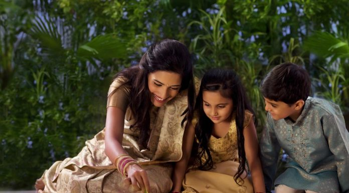 A mother making rangoli with her kids