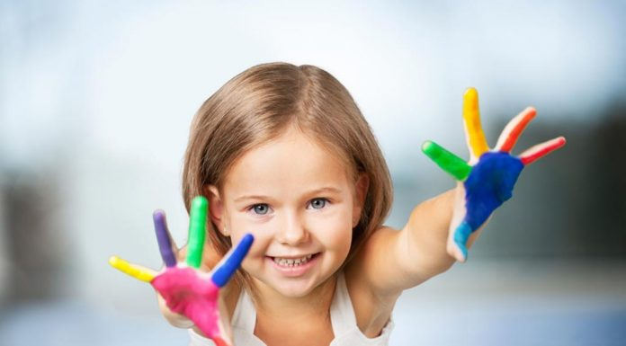 A little girl with paint all over her hands
