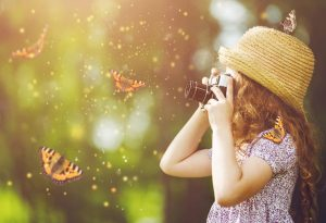 A baby looking at butterflies through a magnifying glass
