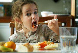 A little girl eating pasta