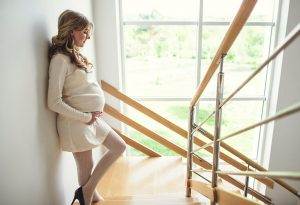 A pregnant woman staring at a flight of stairs