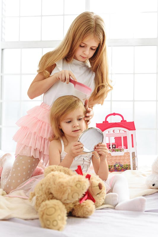 A little girl combing her younger sister's hair