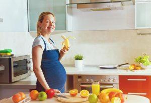 A pregnant woman eating a banana