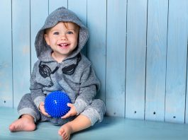 A toddler sitting against a blue wall
