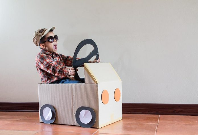 A little boy sitting inside a cardboard car