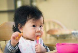 A baby girl eating mashed sweet potatoes
