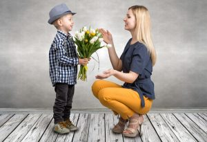 A son giving a bouquet of flowers to his mother