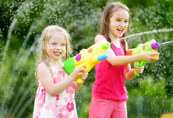 Two little girls playing with water guns