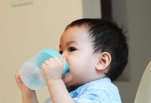 A baby drinking from his cup