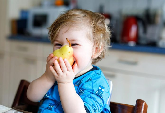 A baby trying to eat pear