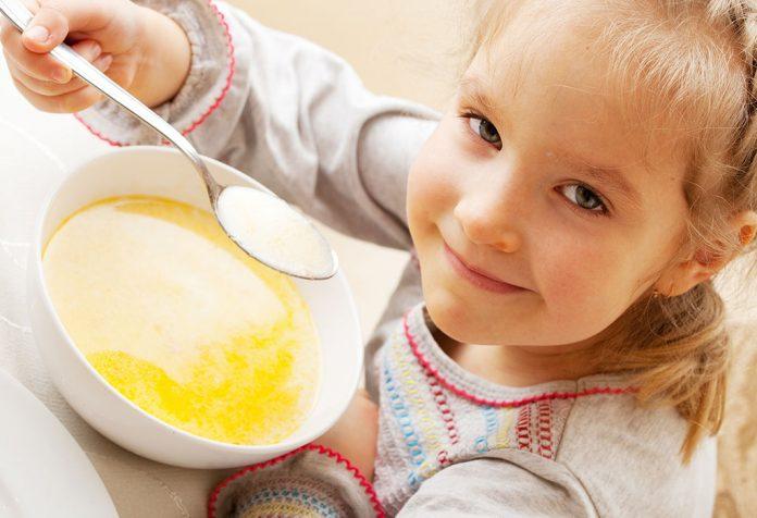 A little girl enjoying a bowl of soup