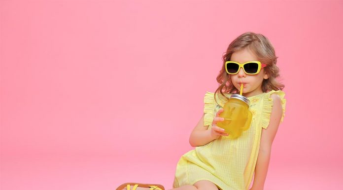 A little girl sipping on a drink from a glass jar