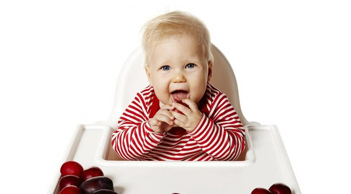 A baby eating plums