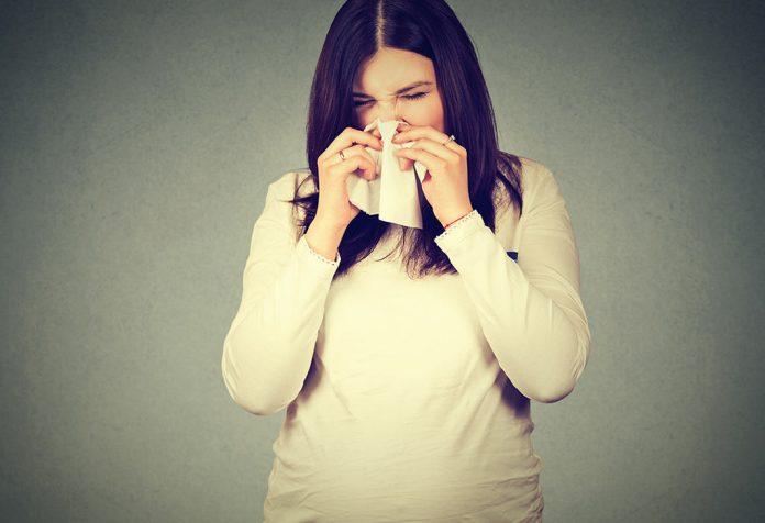 A pregnant woman sneezing