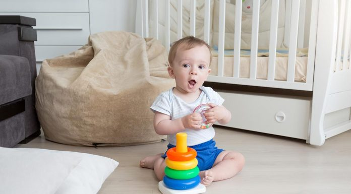 A baby assembling a coloured rings tower