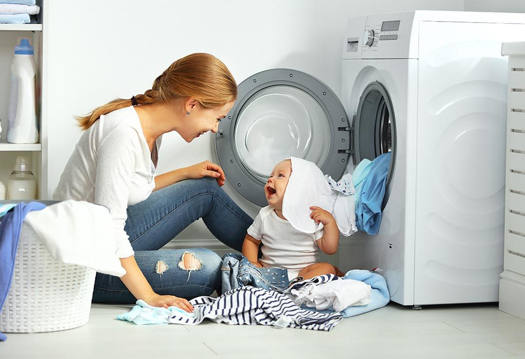 A mother washing clothes while playing with her baby