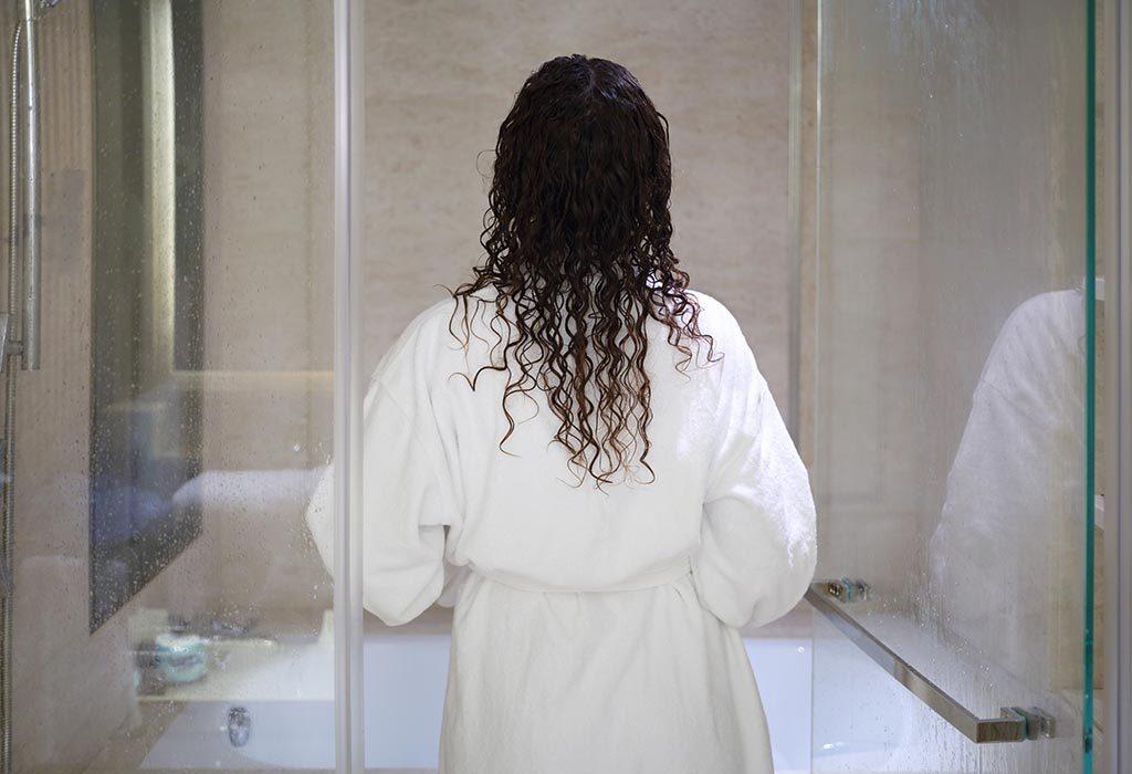 A woman in a bathrobe about to enter the bathroom