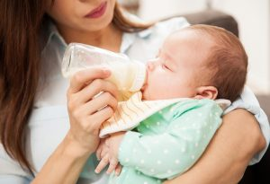A newborn drinking milk from bottle