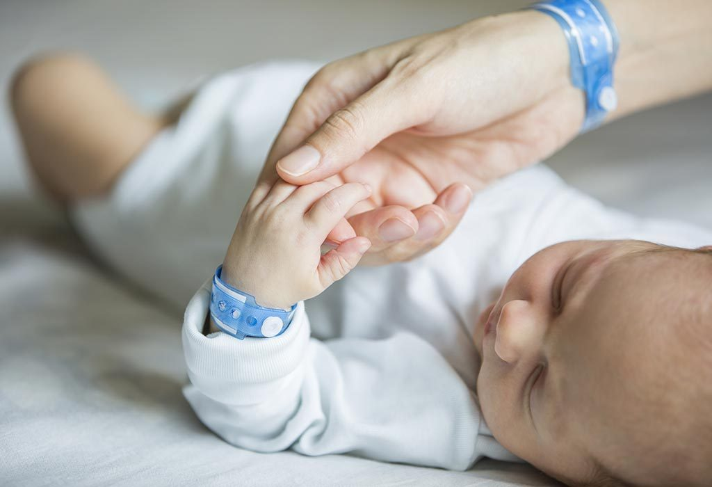 A mother holding her newborn son's hand